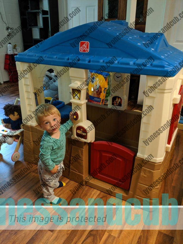 one-year-old playing with Neat and Tidy Cottage Play House from Step2