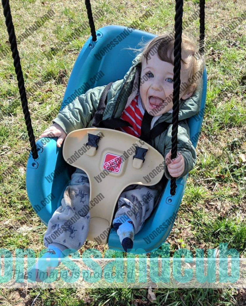laughing toddler having fun in Step 2 baby swing that hangs from a tree