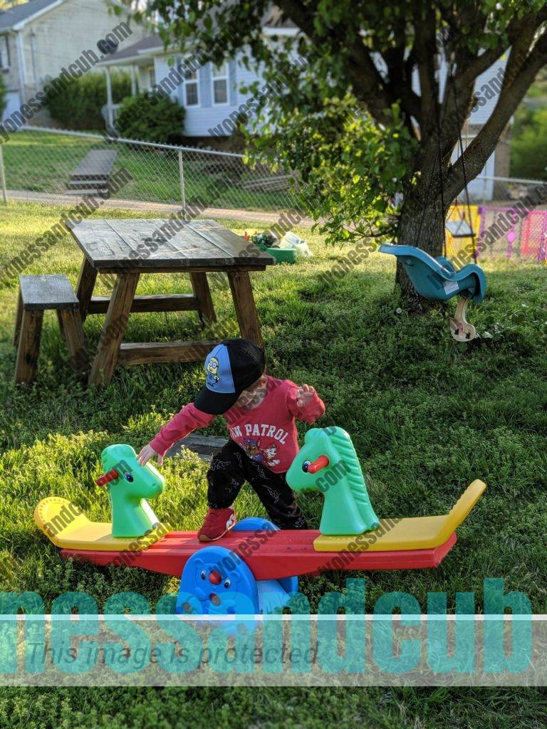 toddler stepping on plastic seesaw