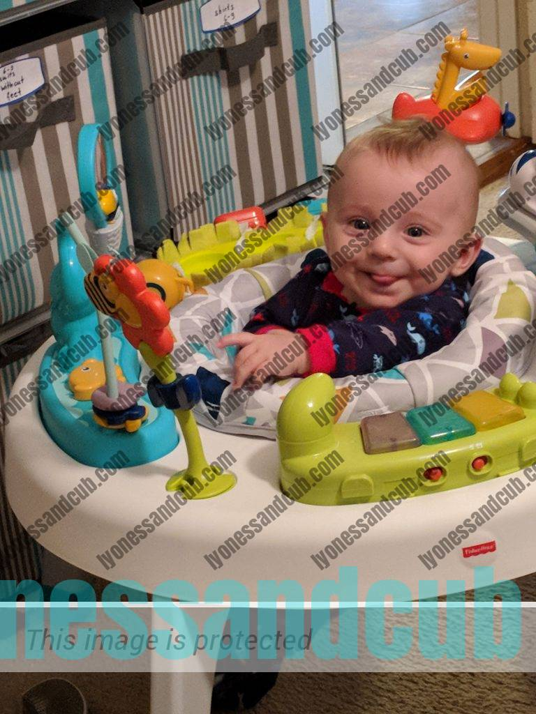 happy baby playing in sit-to-stand activity center