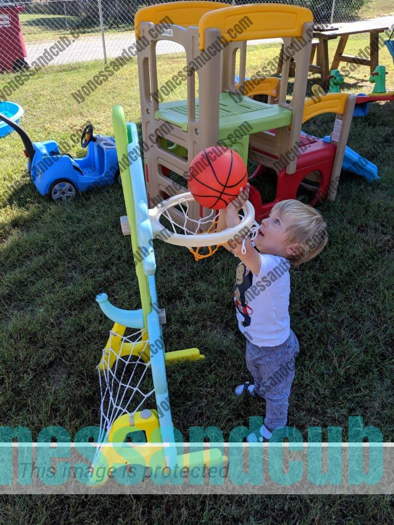 toddler playing with basketball hoop