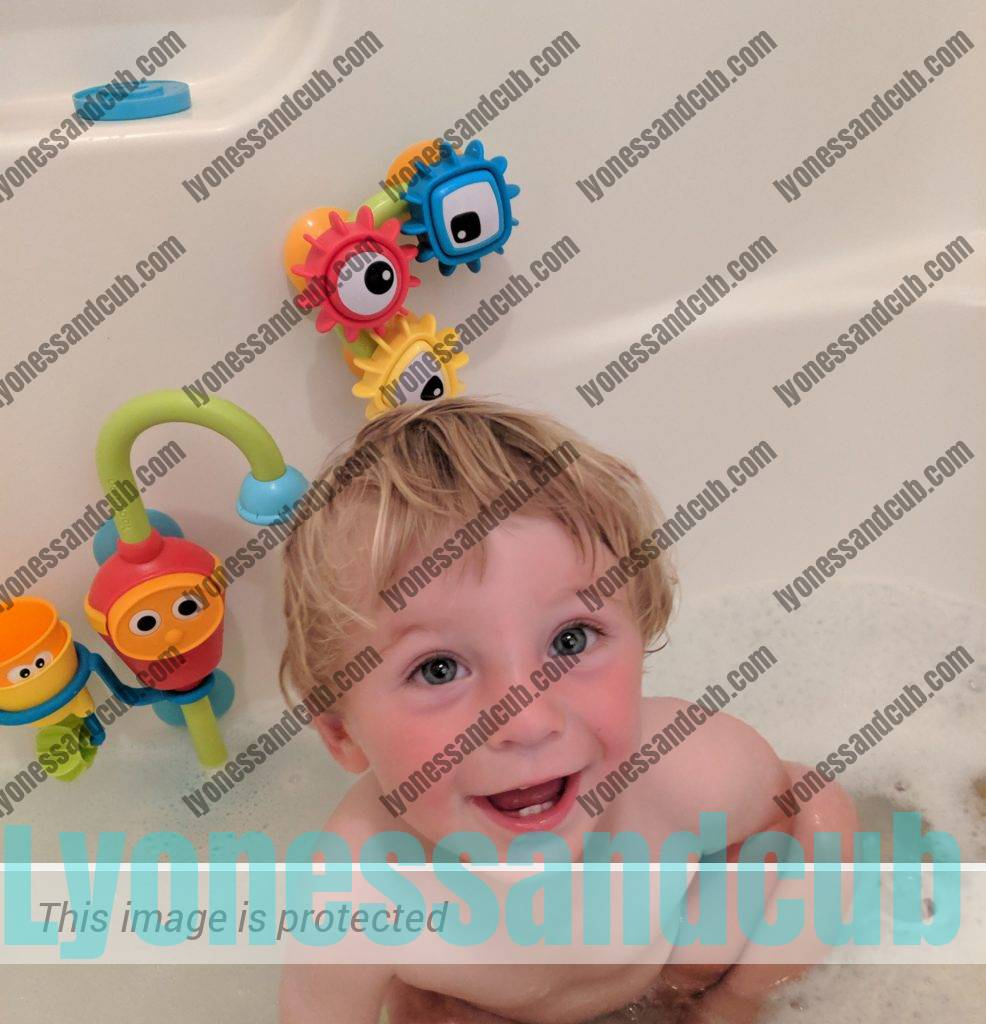 laughing toddler in bathtub with Yookidoo Flow 'n Fill baby bath toy