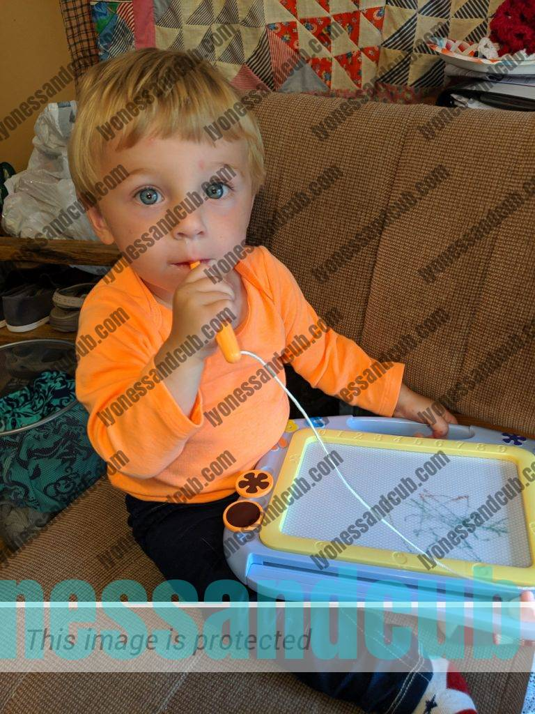 toddler scribbling on magnetic drawing board