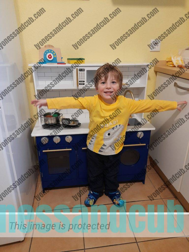 smiling toddler standing in front of wooden toy kitchen, spanning his arms to show how wide it is