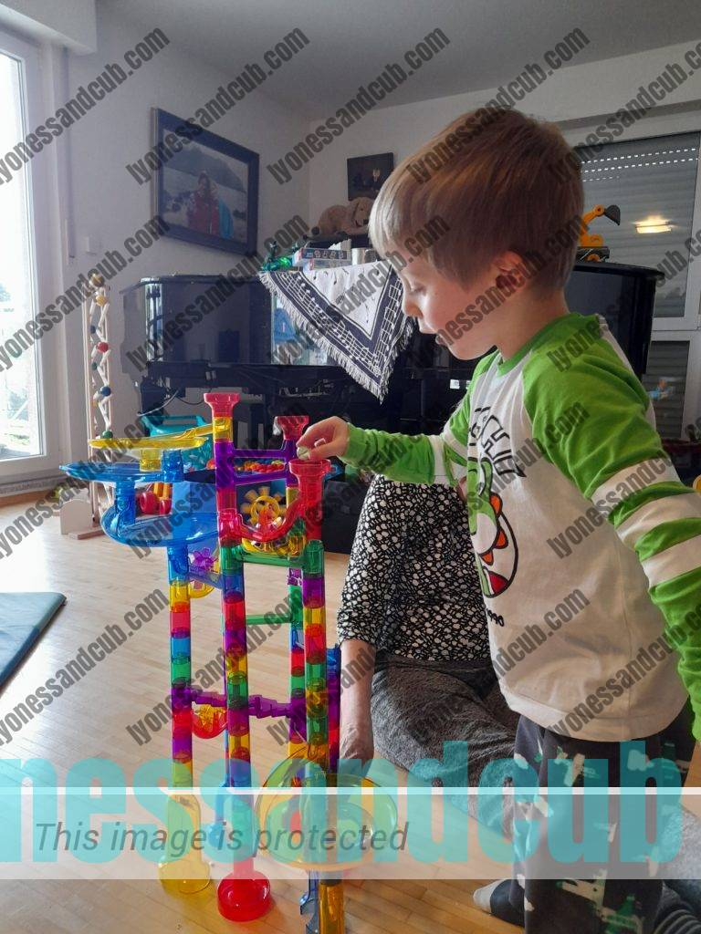 toddler engaged in plastic marble run