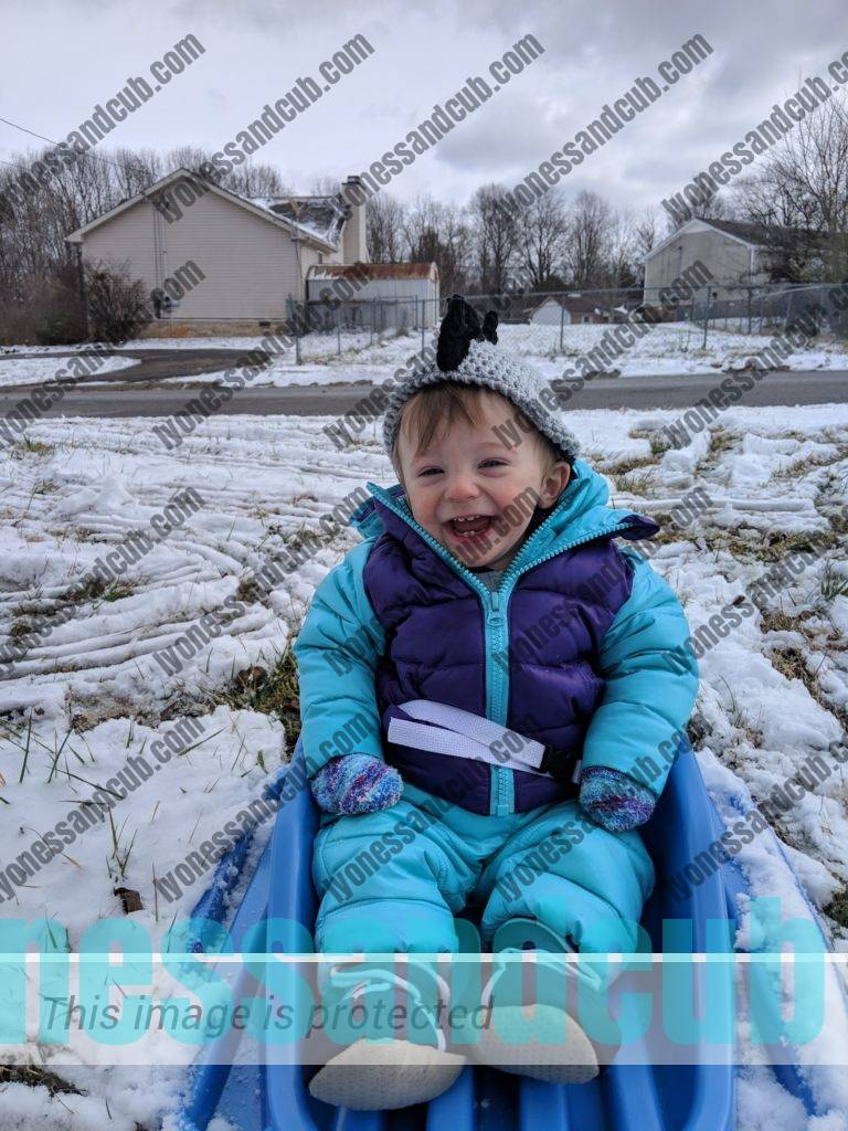 baby sitting in infant sled, laughing, being pulled through the snow