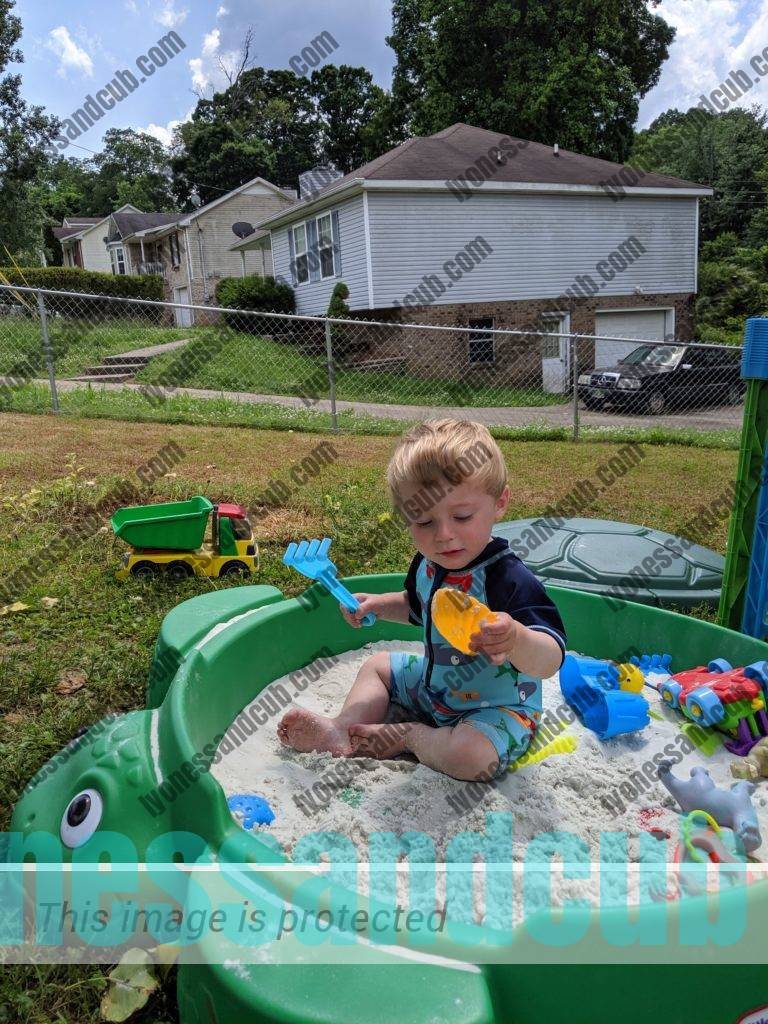 toddler sitting in green turtle sandbox and playing with sand toys