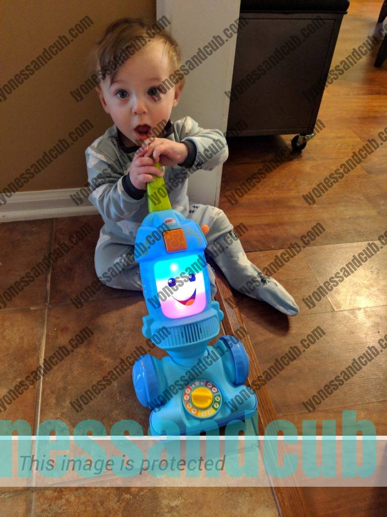 toddler playing with Fisher-Price Laugh & Learn Light-up Learning Vacuum