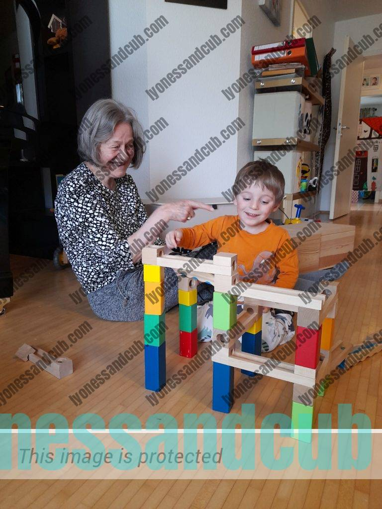 laughing grandma and grandson playing with wooden marble run