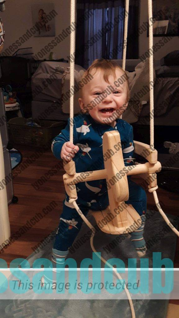 one-year-old sitting in natural wood horse swing, laughing