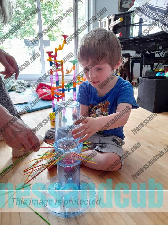concentrated toddler and grandma playing Kerplunk