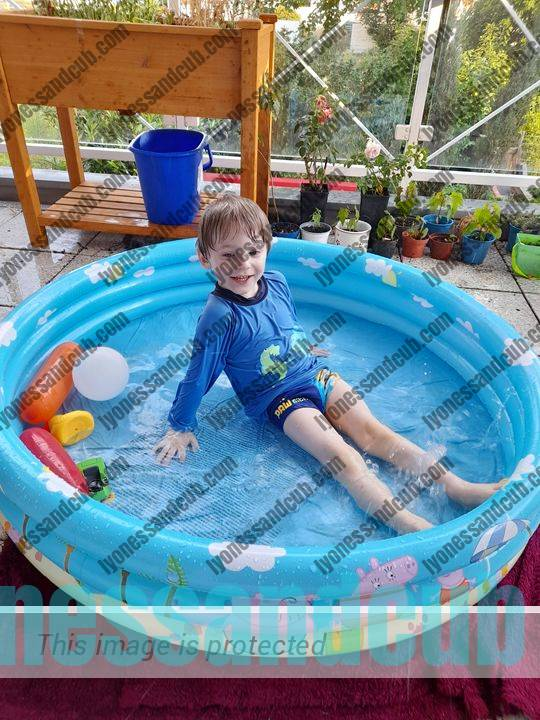 toddler in Peppa Pig pool on balcony