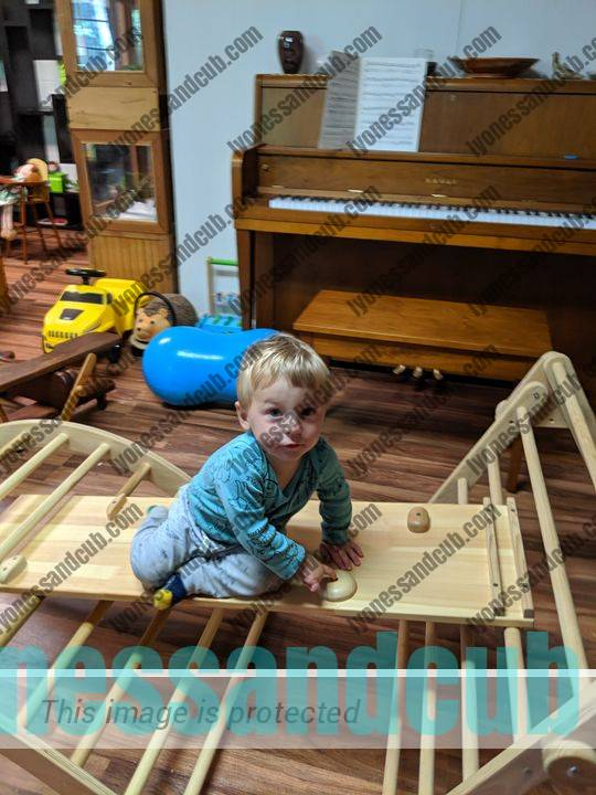 toddler playing on Montessori climbing toys, Pikler triangle, arch, and ramp