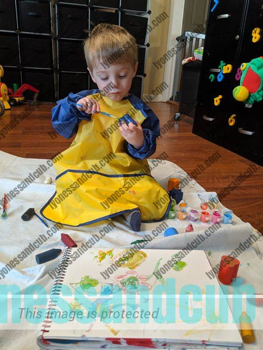 deeply concentrated toddler in long-sleeved painting apron, painting stamps and stamping on paper
