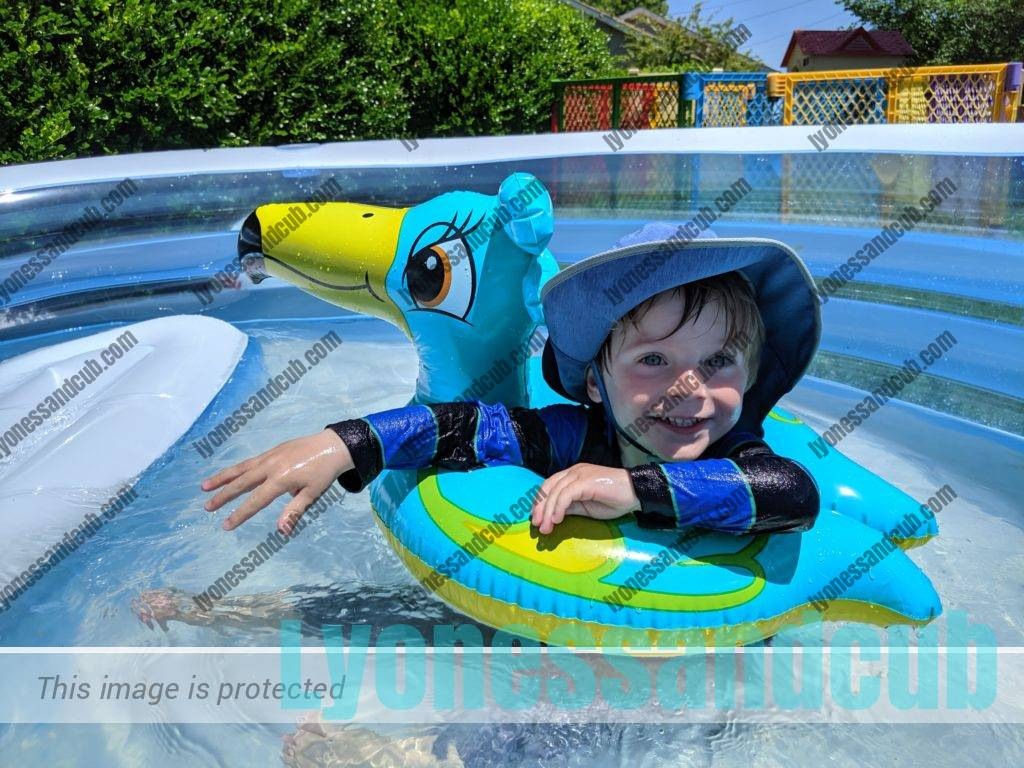 toddler with floating toy pelican, splashing in Intex Swim Center family lounge pool with bench
