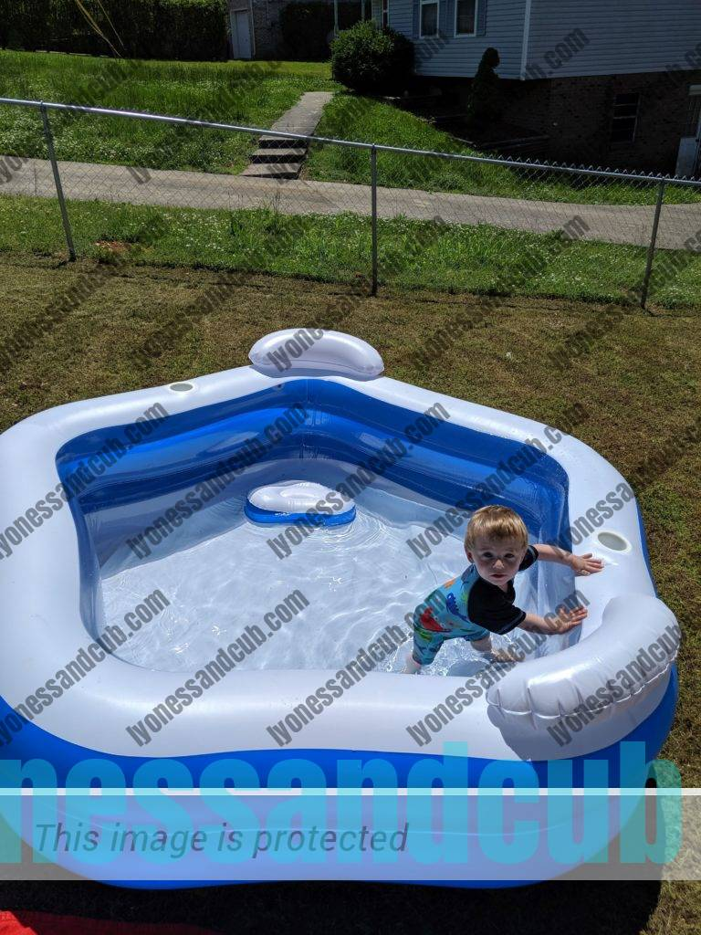 toddler in inflatable pool with seats