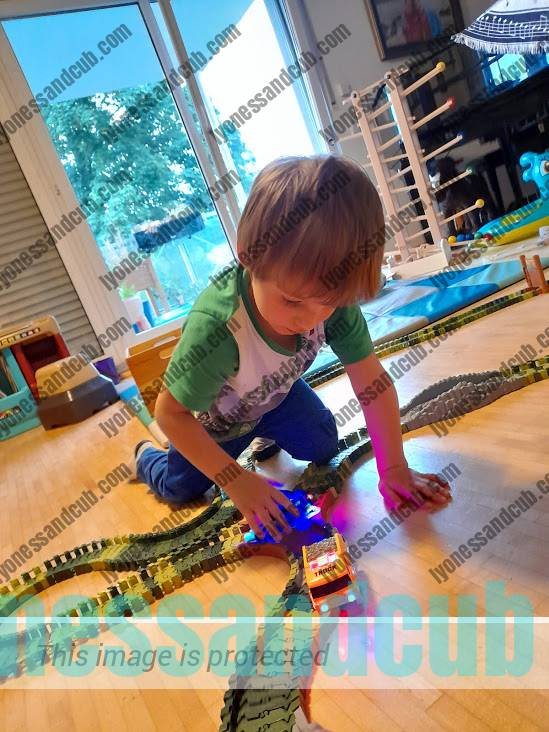 toddler playing with track cars with LED lights