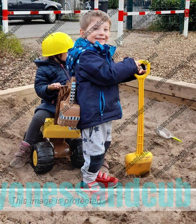 two toddlers in sand box with Mobby Dig ride-on digger