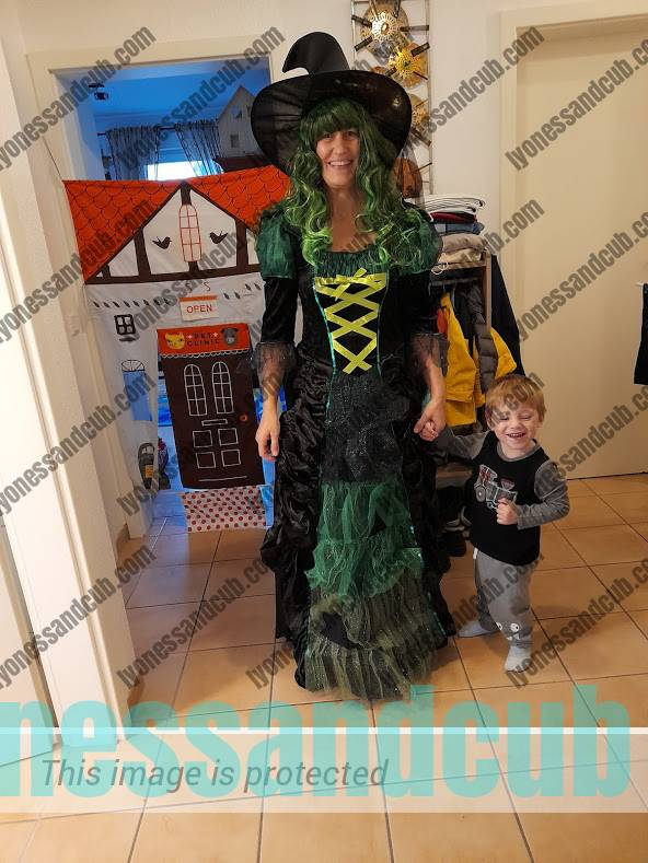 toddler and mommy (in witch costume) standing in front of door frame playhouse