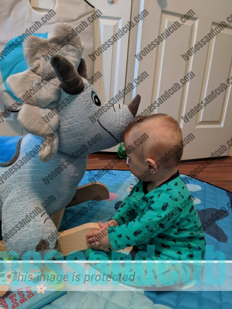 baby with his Fossil Dinosaur Rocker in nursery