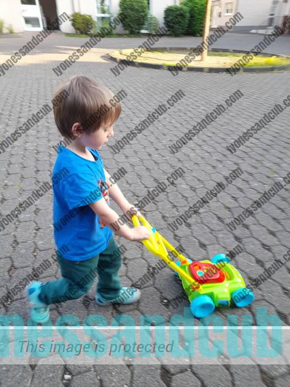 toddler walking with bubble-making lawnmower
