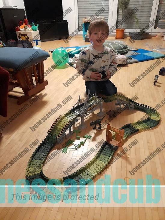 toddler playing with dinosaur race track