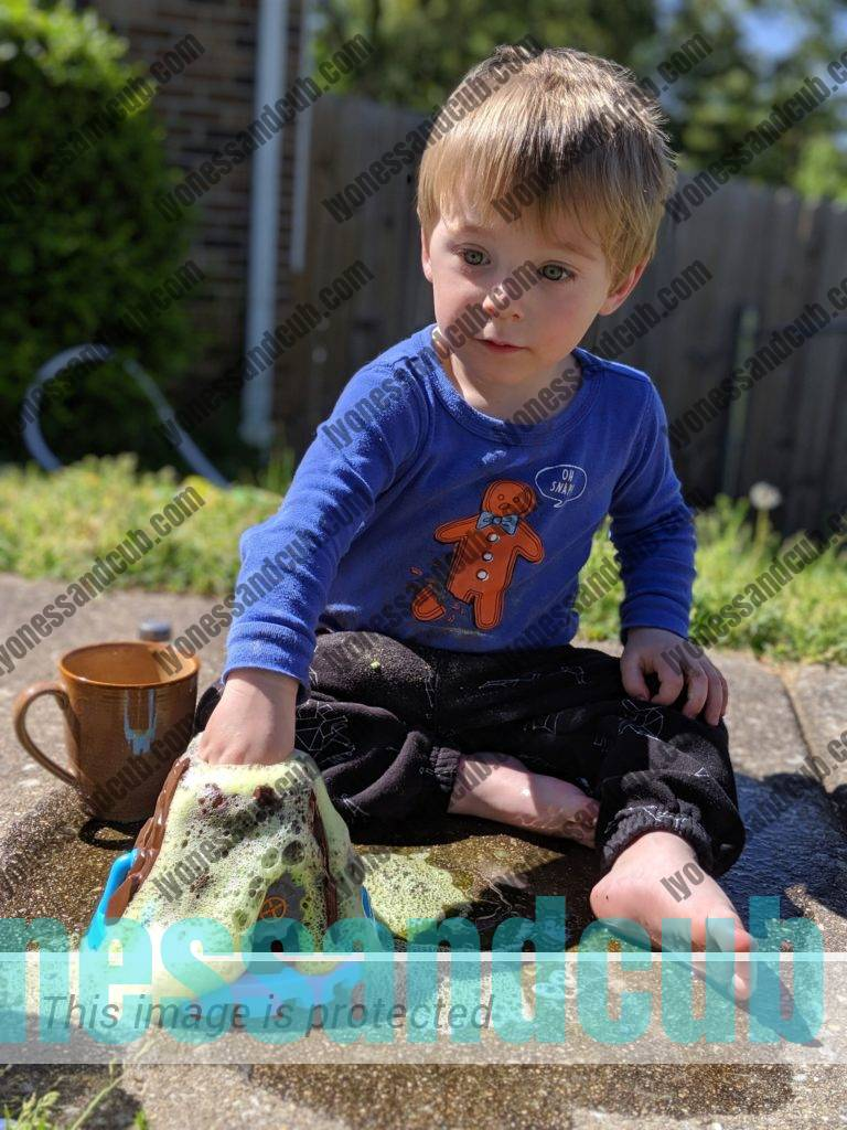 toddler dipping his hand into bubbling volcano containing Beaker Creatures