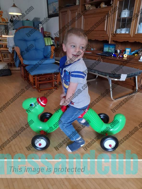 toddler riding on Radio Flyer Inchworm ride-on toy