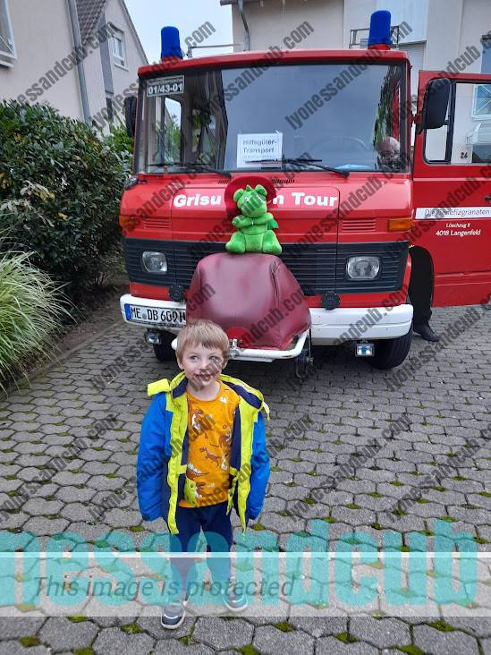 little boy in front of fire engine