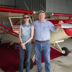 girl and man in front of plane