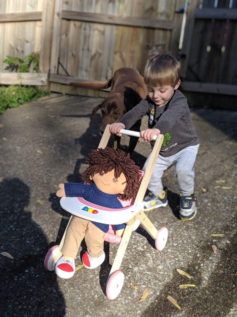 toddler pushing Hape wooden babydoll stroller with boy doll through the yard, followed by Chocolate Labrador Retriever