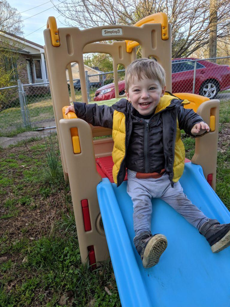 toddler on climbing toy in yard