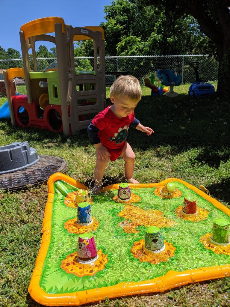toddler stepping on gopher splash mat