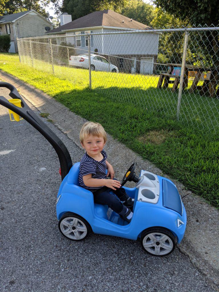 toddler sitting in blue Step2 Whisper Ride ride-on push car