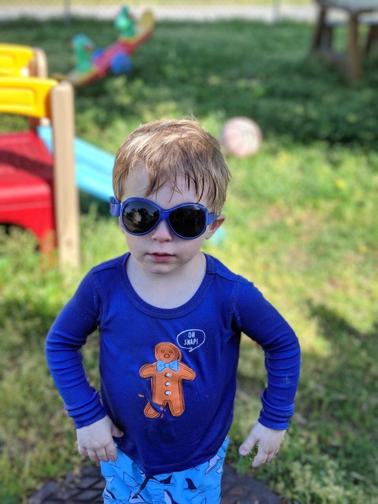 proud toddler wearing Baby BANZ sunglasses