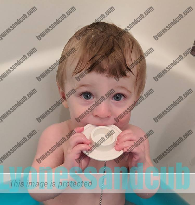 baby chewing on bathtub rubber plug