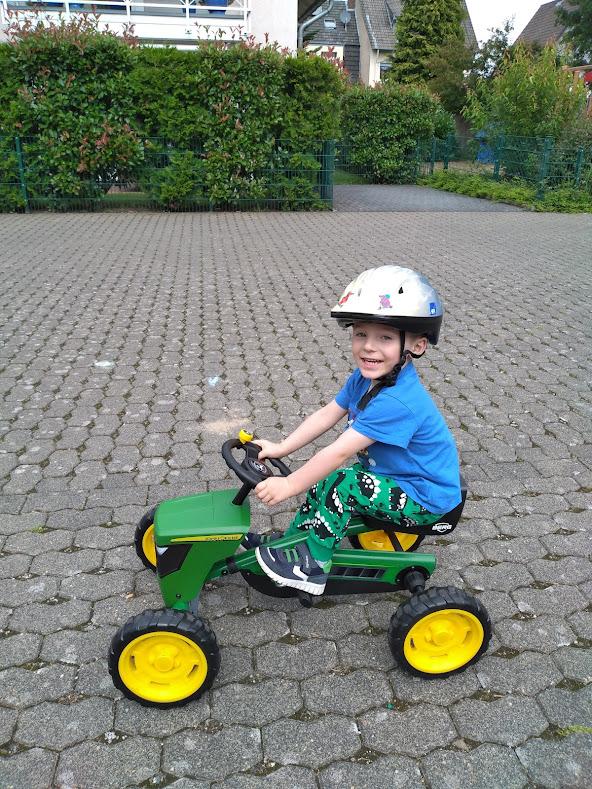 happy toddler riding on John Deere tractor go-kart